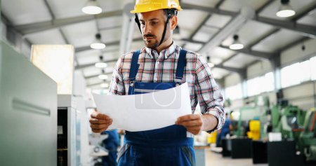 Portrait of an handsome engineer working in metal industry factory