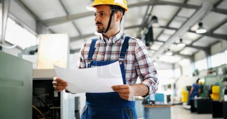 Portrait of an architect builder studying layout plans of industry plant