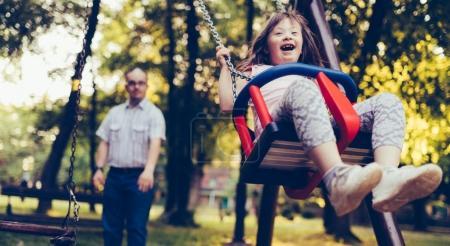 Photo pour Portrait de l'homme et la fille avec le syndrome du duvet balançant dans le parc - image libre de droit