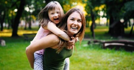 Photo pour Petite fille avec des besoins spéciaux profiter de passer du temps avec la mère dans la nature - image libre de droit