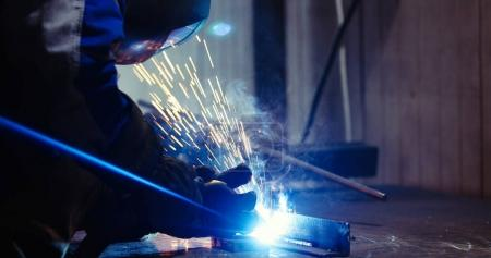 Worker welds at the factory working in metal industry