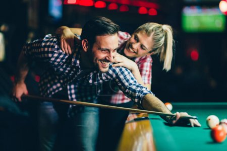 Young attractive couple playing snooker together in bar