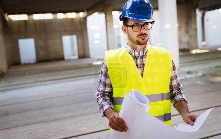 Young business man construction site engineer with blue print