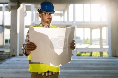 Photo pour Image de l'ingénieur du chantier regardant le plan de construction - image libre de droit