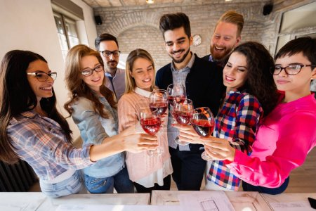 Group of successful architects celebrating together in office