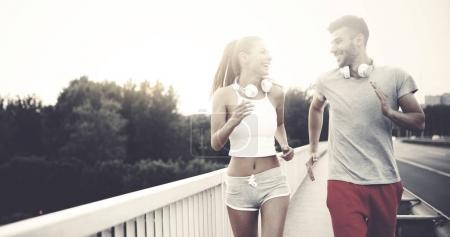 Foto de Hombre atractivo y mujer hermosa trotando juntos en el puente - Imagen libre de derechos