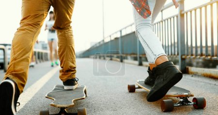Picture of young attractive couple carrying skateboards and having fun