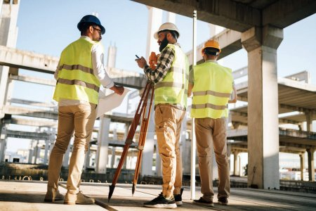Team of construction engineers working on building site together