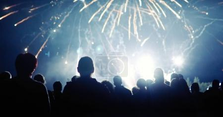 Photo for Crowd watching fireworks and celebrating at night - Royalty Free Image