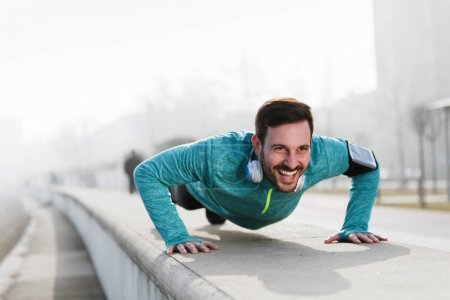 Picture of a young sportsman doing push ups outdoors, fitness and exercising i