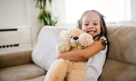 Cute little girl playing with her favorite toy teddy bear