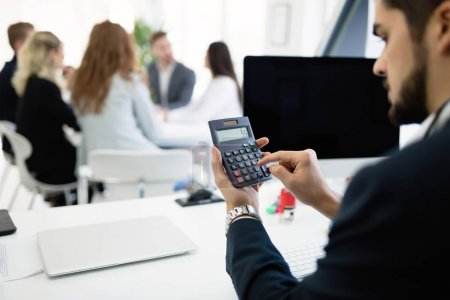Businessman analyzing investment charts with calculator on his office desk