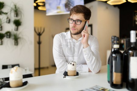 Handsome businessman using phone and wearing glasses in cafe
