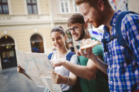 Young happy tourists holding map sightseeing in city