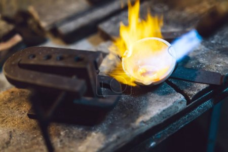 Jeweler melting gold and making jewelry