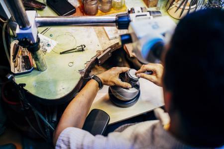 Profesjonalny Jubiler działa na kawałki metalu za pomocą urządzenia optyczne