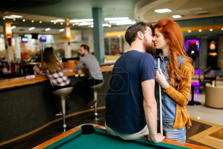 Beautiful couple kissing in billiards bar on their date