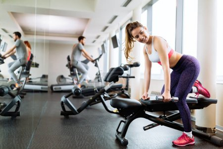 Beautiful woman lifting weights in gym as part of her training