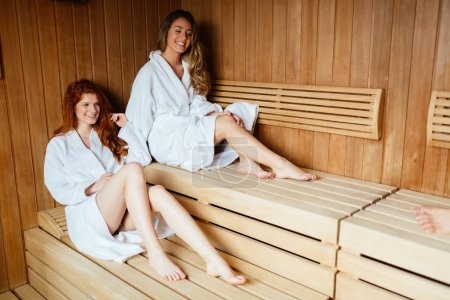 Photo for Beautiful women enjoying sauna treatment in bathrobes - Royalty Free Image