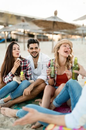 Group of young friends laughing and drinking beer at beach