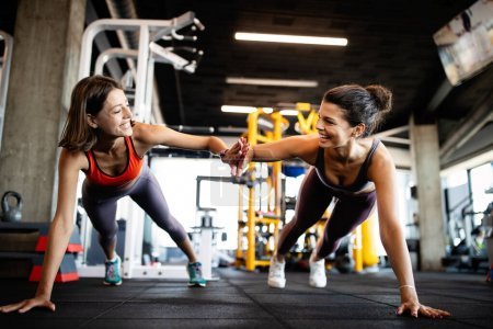 Photo for Attractive fit sports people are working out in gym - Royalty Free Image