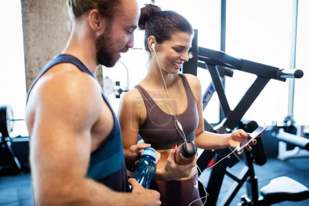 Photo for Young fit woman showing something on smart phone to her male friend in a gym. - Royalty Free Image