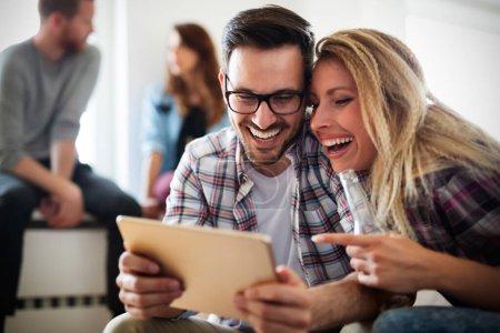 Photo pour Couple joyeux en utilisant une tablette numérique à la maison et de détente - image libre de droit