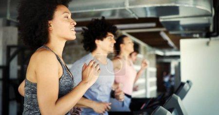 Foto de Jóvenes en forma corriendo en una cinta de correr en el club de salud. - Imagen libre de derechos