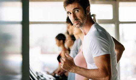 Photo pour Groupe de personnes en forme heureux à la salle de gym exercice - image libre de droit