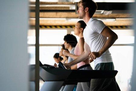 Photo pour Photo de personnes en forme courant sur tapis roulant dans la salle de gym - image libre de droit