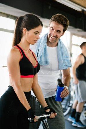 Foto de Retrato del entrenamiento de mujer en forma en el gimnasio con su entrenador ayudando - Imagen libre de derechos