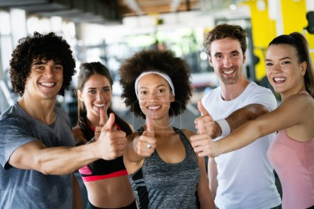 Photo for Diversity group of people training in a gym. Trainer and sportive fit persons exercising in a fitness class - Royalty Free Image