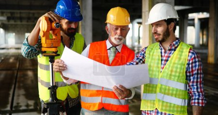 Photo pour Ingénieur, entrepreneur, architecte, investisseur, travail d'équipe. Groupe de travailleurs de la construction parlant et planifiant le travail, tenant le plan directeur - image libre de droit
