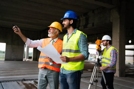 Photo for Confident team of architects and engineers working together on building site - Royalty Free Image