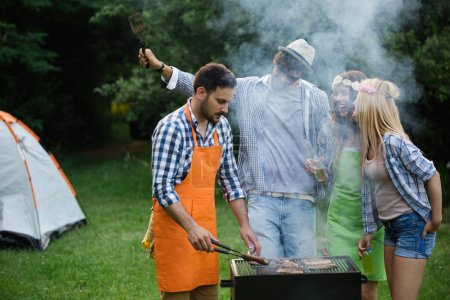 Photo for Group of friends having barbecue party in forest - Royalty Free Image