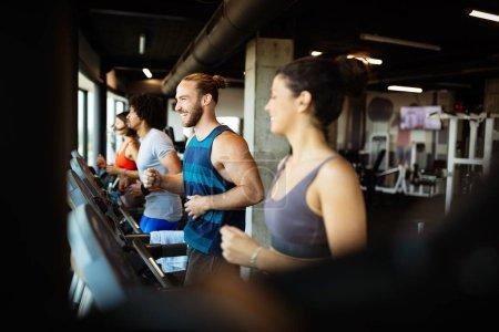 Foto de Ajuste grupo de jóvenes amigos haciendo ejercicio en una cinta de correr en el gimnasio - Imagen libre de derechos