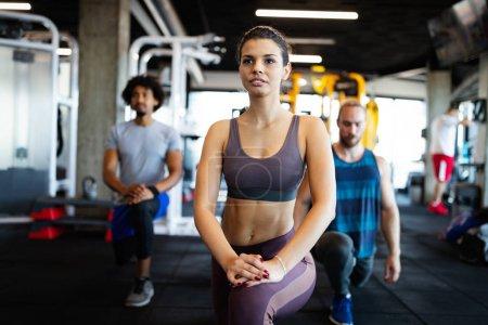 Photo pour Healthy young fit people doing exercises at fitness studio. - image libre de droit