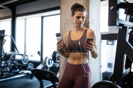 Photo pour Jeune femme en forme à la salle de gym se détendre et écouter de la musique à l'aide d'un téléphone mobile - image libre de droit