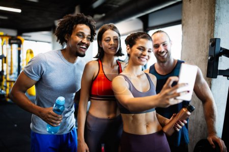 Photo for Group of sportive fit people in a gym taking selfie. Concepts about lifestyle and sport in a fitness club - Royalty Free Image