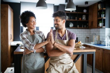 Photo for Young happy african couple in aprons giving high five in kitchen - Royalty Free Image
