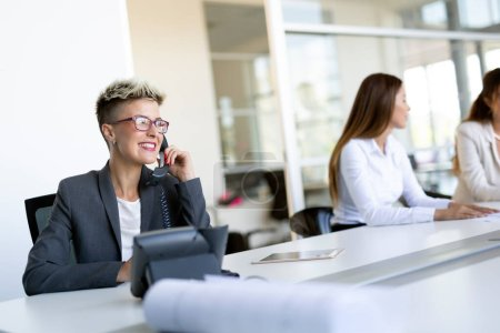Photo for Beautiful businesswoman working sitting at her desk in the office - Royalty Free Image