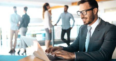Photo pour Bel homme d'affaires travaillant sur ordinateur portable au bureau - image libre de droit
