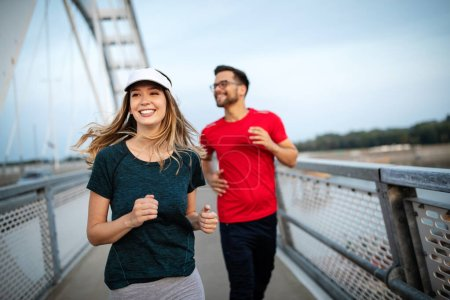 Sport couple. Young man and woman jogging outdoor ...