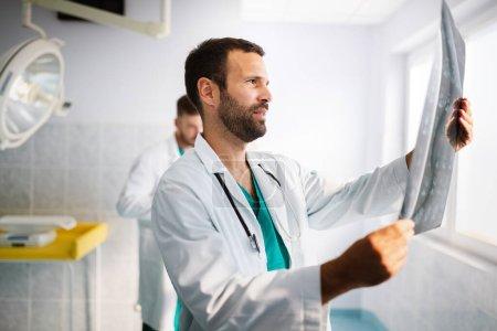 Photo pour Portrait de beau jeune médecin vérifiant les rayons X à l'hôpital pour faire un diagnostic - image libre de droit