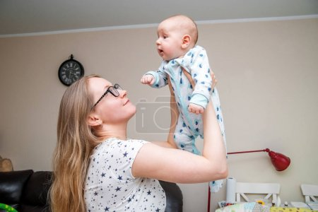 A young woman with a baby in the living room.