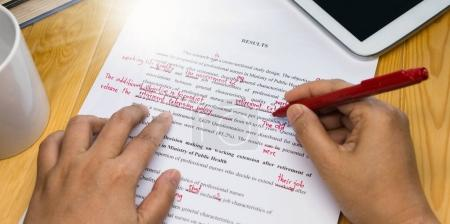 Hand holding red pen over proofreading text on tab...