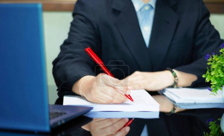 Hand holding red pen to proofread on black table i...