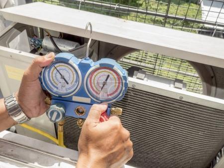 Photo pour Seul homme tenir manomètre, équipement de mesure de climatiseur sur sa main sous la lumière du soleil sur le balcon - image libre de droit