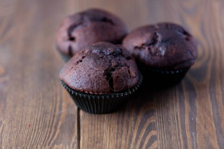 Photo for Chocolate muffin on wooden table - Royalty Free Image