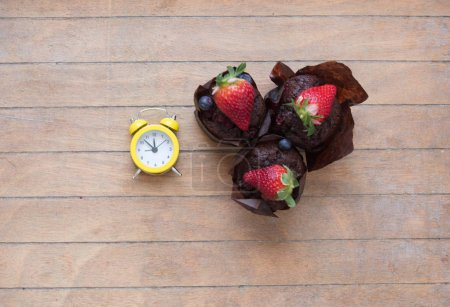 muffins with berries and alarm clock